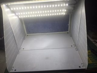 The fully lit airbrush spray booth with the LED light strips installed and powered on